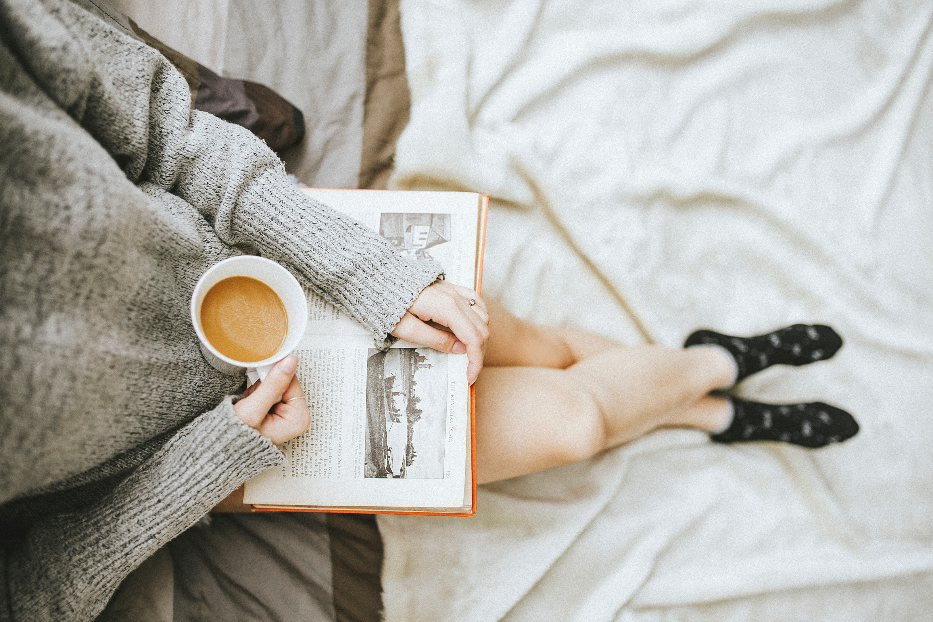 Woman sitting with a book and a cup of coffee